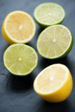 Vertical shot of halved lemons and limes on black wooden surface