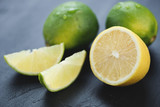 Whole and sliced limes and lemons, black wooden background