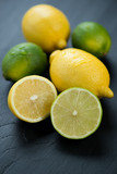 Ripe lemons and limes over black wooden background