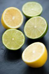 Vertical shot of halved lemons and limes on black wooden surface