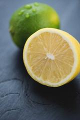 Sliced lemon and whole lime, close-up, vertical shot