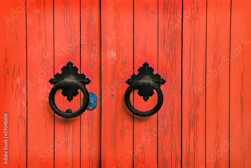 Red wooden door with round handles