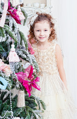little girl decorates a Christmas Christmas tree