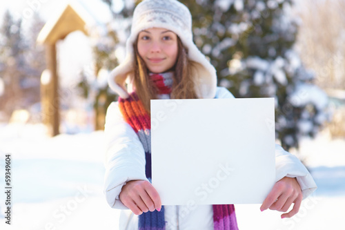 Young beautiful girl with blank banner. Winter.
