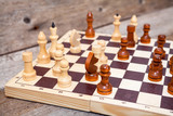 Unfinished chess game on wooden board