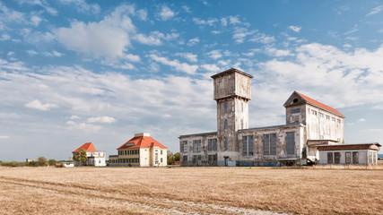 alter verfallener Flughafen vor bewölkten blauen Himmel
