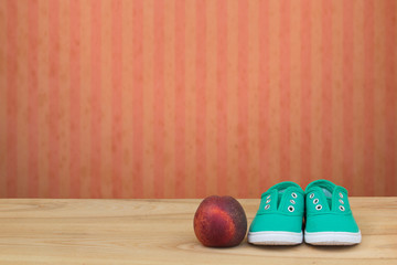 Green sneakers and a peach on a wooden table and red grunge wall