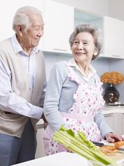 loving senior couple preparing meal in kitchen