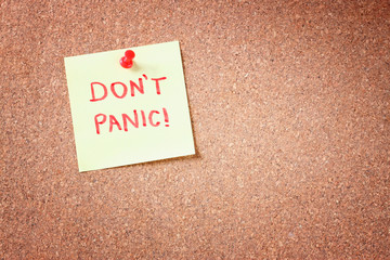 "cork board with pinned yellow note and the phrase ""dont panic"" w"