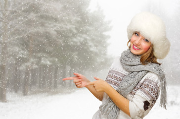Young girl shows pointing gesture at snowy forest