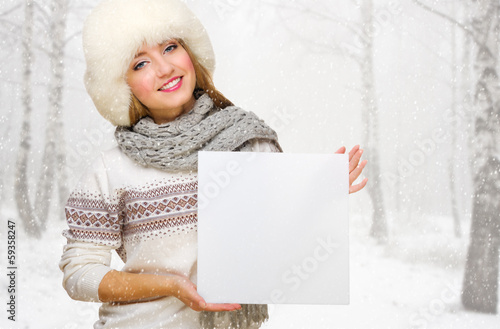 Young girl with empty card at snowy forest