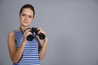 girl with binoculars isolated on grey background