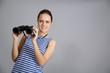 girl with binoculars isolated on grey background