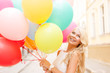 smiling woman with colorful balloons