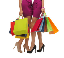 two women in pink dresses with shopping bags