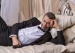 Elegant playboy reclining on a bed