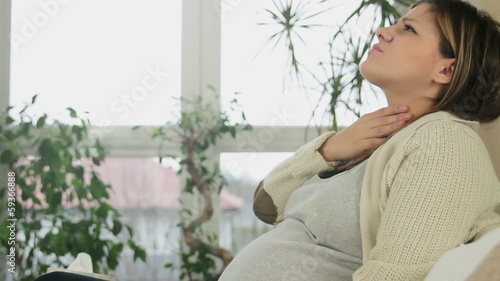 Young pregnant woman with sore throat, indoors