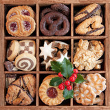 Assorted Christmas cookies in wooden box with holly sprig