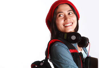 female student with headphones and holding a laptop