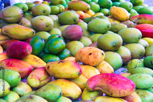 Fresh Mango: green, red, yellow in the local market on Mahe
