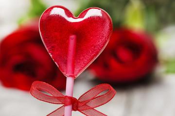 Lovely red lollipop in heart shape. Symbol of sweet love