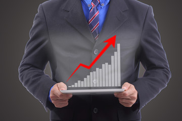 Businessman hold growing red graph