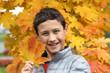 boy holding a maple leaf in falling