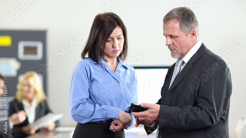 Business man showing woman smartphone in office