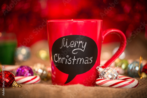 Red ceramic cup with Merry Christmas sign made with chalk.