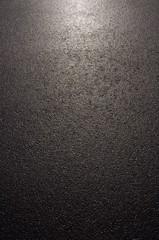 Hintergrund nasser Asphalt im Gegenlicht