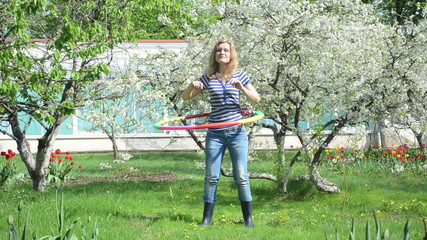 woman spin hula hoop ring in spring garden