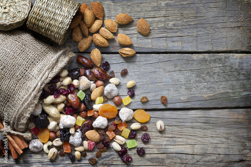 Nuts and dried fruits on vintage wooden boards still life