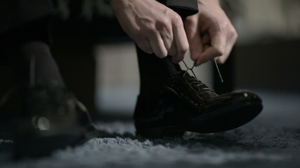 Man tying shoes.