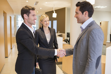 Smiling Business partners shaking hands in hall, lobby