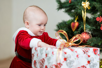 baby in front of Christmas tree with big gift box