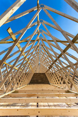Wood house truss against blue sky