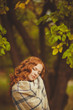 Portrait of young beautiful redhair woman standing in green park