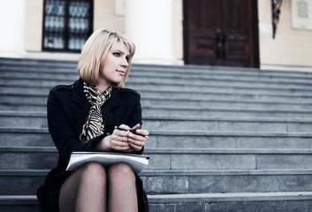 Young businesswoman with notebook sitting on the steps