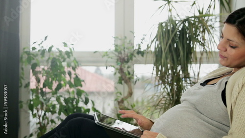 Pregnant woman using a tablet pc, tracking shot