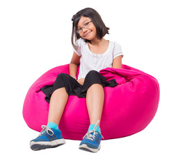 Little Asian girl relaxing on a bean bag over white background