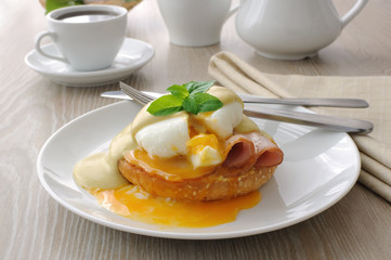 eggs (poached) with ham on a bun with sauce