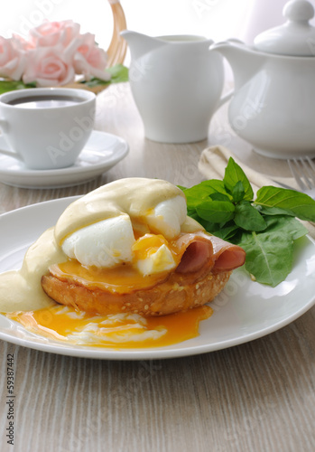 Boiled eggs (poached) with ham on a bun with sauce