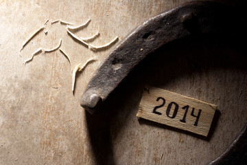 2014 year - horseshoe on a wooden background