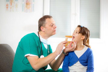 Pediatrician checking little girl throat