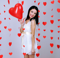 Attractive young woman with balloons in room on Valentine Day