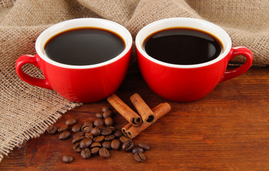 Red cups of strong coffee and coffee beans