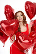 Beautiful fashion woman posing with red ballons