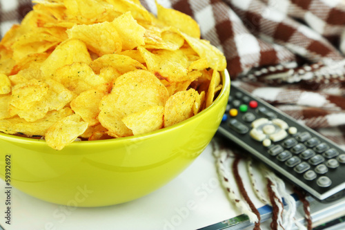 Chips in bowl, magazines, plaid and TV remote close-up