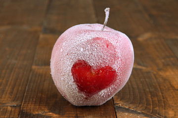 Holiday apple with frosted heart on wooden background