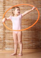 Little girl holding hula hoop.